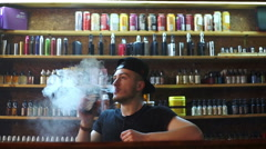 Vape shop seller show e-cigarettes to buyer and exhaling smoke Stock Footage