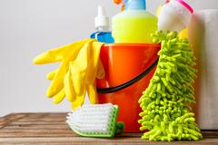 Bucket with cleaning items on light background Stock Photos
