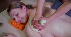 Using a herball compress ball on the young woman's back Stock Footage