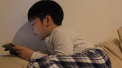 Asian boy playing smart phone in the room - stock footage