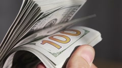 Hand leafing through a stack of dollar bills. Slow motion Stock Footage