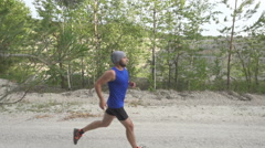 Slow motion.  Male runner exercising and training outdoors in nature. traill- Stock Footage