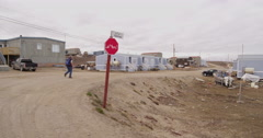 Tourist walks on road in inuit town of Pond Inlet Stock Footage