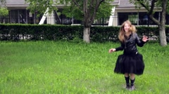 Teenage girl jumping and spinning crazy emotions in park Stock Footage