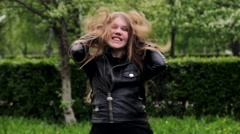 Beautiful teenage girl long blond hair moving dancing crazy emotions in park Stock Footage