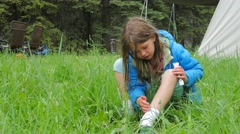 Little girl camping and putting itch cream on leg Stock Footage
