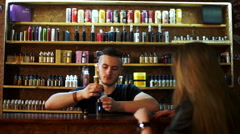 Seller in vape shop shows to young girl e-cigarettes and showing how it works Stock Footage