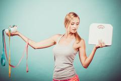 Girl with scales measuring tapes. Weight loss. - stock photo