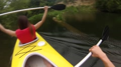 Two people canoeing in the river in the beautiful green water park in the rain Stock Footage