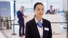 4K Portrait friendly smiling bank employee with colleagues working in background Stock Footage