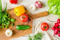 Organic food background. Vegetables on the chopping board Stock Photos