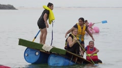 Children fix a sinking raft - youth & future environmental problems - stock footage