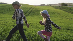 Children are walking by the green meadow. Little girl walks like a soldier. Stock Footage