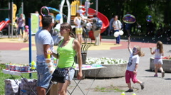 Selling bubble blower in a park seller attract advertising kids to buy Stock Footage