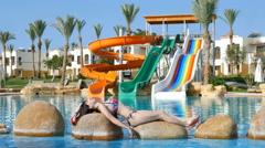 beautiful girl resting, sunbathing by the pool - stock footage