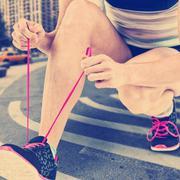 Athlete tying her shoe lace against new york street Kuvituskuvat