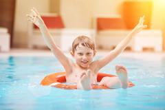 Happy boy swiming in pool Kuvituskuvat