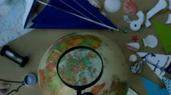 4k holiday and travel composition with a magnifying glass on globe - stock footage