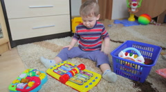 The child sits on the floor among the toys and dance Stock Footage