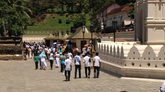 People walk by the territory of the Dalada Maligava temple in Kandy, Sri Lanka. Stock Footage