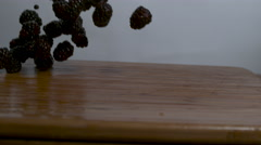 Blackberries falling and rolling onto a cutting board in slow motion Stock Footage