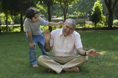 Grandson tickling grandfather in ear Stock Photos