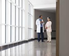 Doctor discussing patient care in hospital corridor Stock Photos