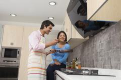 Smiling couple preparing food in kitchen Stock Photos