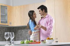 Smiling couple dancing while preparing salad in kitchen Stock Photos