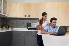 Smiling couple using laptop in kitchen Stock Photos