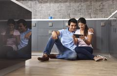 Full length of smiling couple using digital tablet in kitchen Stock Photos