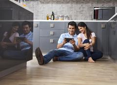 Full length of smiling couple using digital tablet together in kitchen Stock Photos