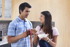 Smiling couple having coffee and pasta in kitchen Stock Photos