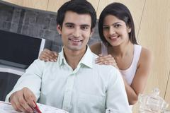 Portrait of smiling young couple in kitchen Stock Photos