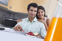 Portrait of smiling couple with catalogues and apple at kitchen island Stock Photos
