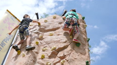 Healthy lifestyle family festival - children kids climbing the wall gym in park Stock Footage