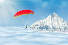 Freestyle solo paragliding over clouds against mountain peak - stock photo