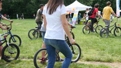 Young teen age people ride walk with bicycle for trial freestyle cycling in park Stock Footage