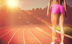 Close up of sportswoman legs with sweat against composite image of race track - stock photo