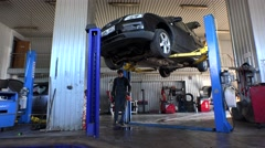 service man spray and wash oil remain on floor in car repair garage. - stock footage