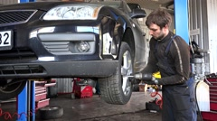 Mechanic removing tire bolts with electric tool. Stock Footage