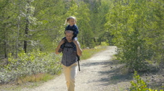Daughter sits on the shoulders of his father walking outdoors on a forest pat - stock footage