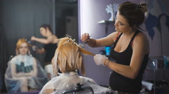 Professional hair coloring beauty studio. The girl in the client chair looking Stock Footage