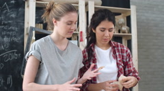 Tilt down of two young craftswomen putting glued pieces of craft paper into p Stock Footage