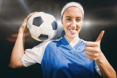 Portrait of happy woman football player holding a football  against spotlight - stock photo