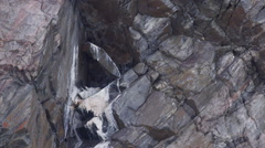 Rare gyre falcon sits on nest in jagged cliff Stock Footage