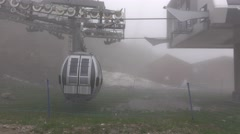 Gondola lift arrive to middle station, descend from cloudy air, pass by pylon Stock Footage
