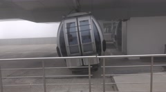 Gondola lift arrive to station, doors open, people come out, trucking shot Stock Footage