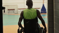Silhouette of a Man on a Wheelchair Arriving at a Basketball Court Stock Footage