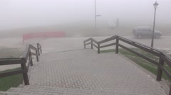 POV walk down at wide staircase, foggy area at high altitude. Alpine ski resort Stock Footage